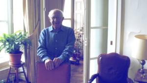 Claude Alaphandéry dans son salon, debout derrière un fauteuil